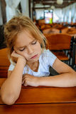 Sad little girl sitting at a wooden table Stock Photos