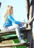 Sad little girl on a slide. Sad kid - hairy blonde girl in blue t-shirt, blue jeans and grey socks sitting on top of green slide Stock Images