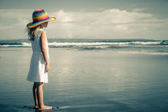Sad little girl standing at the beach stock photography