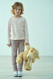 Sad little girl standing with bear Stock Images