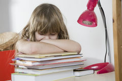 Sad little girl studying at the desk Stock Photo