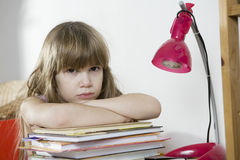 Sad little girl studying at the desk Royalty Free Stock Photography