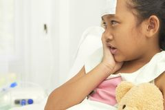 Sad little girl suffering from toothache. Thai Little beautiful girl lying in bed and holding her cheek with a sick tooth Royalty Free Stock Photos
