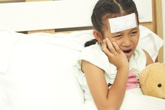 Sad little girl suffering from toothache. Thai Little beautiful girl lying in bed and holding her cheek with a sick tooth Stock Photos
