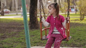 Sad little girl swinging on a swing stock video