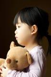 Sad little girl with teddy bear. Sad little girl holds a teddy bear looks into the window. Resentment and expectation Royalty Free Stock Photos