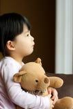 Sad little girl with teddy bear. Sad little girl holds a teddy bear looks into the window. Resentment and expectation Stock Photography