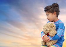 Sad little girl with teddy bear over evening sky. Childhood, sadness, loneliness and people concept - sad little girl with teddy bear toy over evening sky royalty free stock image