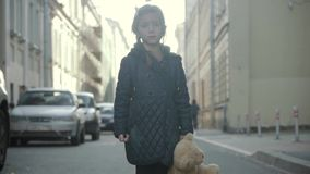 Sad little girl with teddy bear staying in the street, turning and go away. stock footage