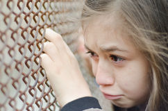 Sad little girl under fence Stock Photography