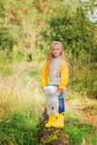 Sad little girl walks in the autumn forest in the raincoat. she holds a favorite toy in his hands. Stock Photography