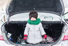 Sad little girl in warm clothes standing in open trunk of car in winter Royalty Free Stock Photography