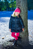 Sad little girl in warm clothes standing in park Stock Image