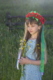 Sad little girl with wild flowers Stock Photos