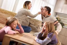 Sad little girls screaming while her parents are arguing in the. Sad girls while parents quarreling at home,disrupted and confict family relationships concept Royalty Free Stock Photography