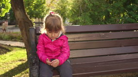 Sad little kid sitting on a bench in the Park. stock footage