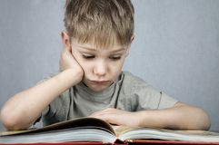 Sad little reader Stock Image