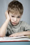 Sad little reader. Little sad boy with big book royalty free stock photos