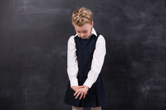 Sad little schoolgirl near blackboard Royalty Free Stock Images