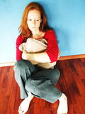 Sad and Lonely. A young girl sitting by herself on the floor at home and being sad Stock Photo