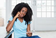 Sad and lonely african american woman waiting for message. On phone indoor at home stock photography
