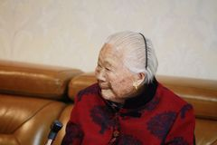 Sad and lonely Asian Chinese old woman 90s. Sad and lonely Asian Chinese old woman, 93 years old, up to 90s , silvery hair, golden earing on her ear Royalty Free Stock Photo