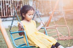 Sad and lonely asian little child girl sitting on swings. In playground in vintage color tone Royalty Free Stock Photos