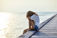 Sad lonely beautiful woman sitting on the pier. With copy space Royalty Free Stock Photo