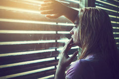 Sad and lonely blonde woman with wet hair. Looking through window blinds into the sunlight Stock Photography