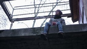 Sad lonely boy sitting alone on edge of abandoned roof, transitional age crisis. Stock footage stock footage