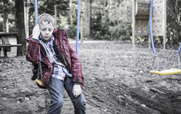 Sad lonely boy sitting on swing. Boy who feels alone. Is different then the rest. being bullied. Sitting sad alone on playground swing after school time Royalty Free Stock Photo