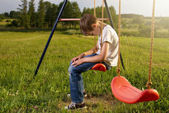Sad lonely boy sitting on swing. Alone Stock Photo