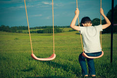 Sad lonely boy sitting on swing. Back view Stock Photo