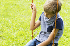Sad lonely boy sitting on swings. Close up. Sad lonely boy sitting on swings at outdoor playground. Close up. Sad, lonely, depressed, unhappy mood Royalty Free Stock Photography