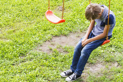 Sad lonely boy sitting on swings. Sad lonely boy sitting on swings at outdoor playground. Sad, lonely, depressed, unhappy mood Royalty Free Stock Photography