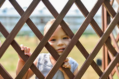 Sad and lonely child looking out through fence. Social problems, family abuse, children stress negative emotions. Sad and lonely child looking out through fence Royalty Free Stock Photography
