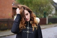 Sad lonely depressed young woman ruffling her hair. Outdoors on suburban street in Germany Royalty Free Stock Images