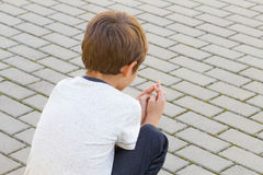 Sad, lonely, disappointed child sitting alone on the ground outdoor. Sad, lonely, unhappy, disappointed child sitting alone on the ground outdoors Royalty Free Stock Image