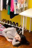 Sad lonely fashionable girl lying on floor under her clothes and shoes Stock Photography