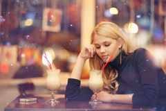 Sad lonely girl drinking coffee in a cafe. At night Royalty Free Stock Photography