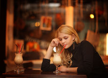 Sad lonely girl drinking coffee in a cafe. At night Stock Photo