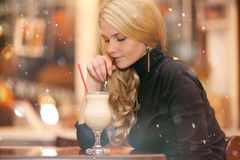 Sad lonely girl drinking coffee in a cafe. At night Stock Images
