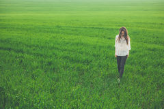 Sad lonely girl in green field. Outdoor full body portrait of sad lonely girl in green field. Young woman walking in meadow with copy space royalty free stock photos