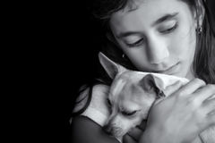 Sad lonely girl hugging her small dog. Emotional black and white portrait of a sad lonely girl hugging her small dog Stock Images