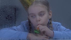 Sad lonely girl with party blower looking in window on rain, having no friends. Stock footage stock footage