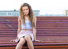 Sad lonely girl sitting on a bench a warm summer day in the city Stock Images