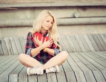 Sad lonely girl sitting on wood planks and hugging a big red heart Royalty Free Stock Photos
