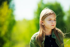 Sad lonely girl. Staying in the forest and hair blowing in the wind Royalty Free Stock Images
