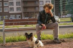 Sad lonely guy sitting on a bench with his dog. the difficulties of adolescence in communication concept. Street stock photography