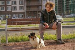 Sad lonely guy sitting on a bench with his dog. the difficulties of adolescence in communication concept. Street royalty free stock photos